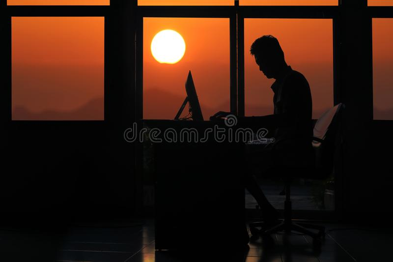 Silhouette business man working on a computer with sunset stock photo