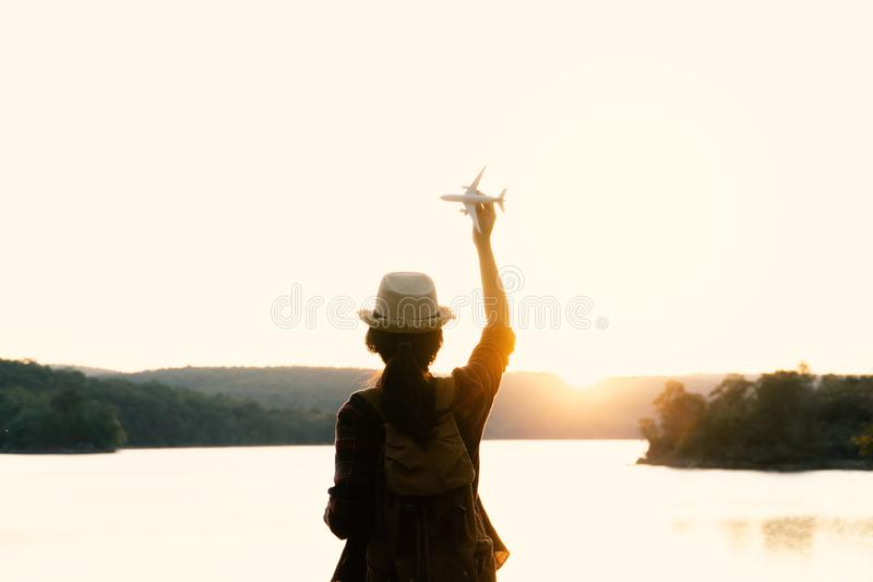 Silhouette Asian woman backpack with airplane model on the park background royalty free stock photo