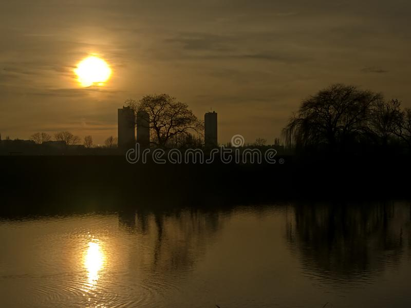 Silhouette of askyscrapers of trees along river Scheldt against evening sky with sun stock photo