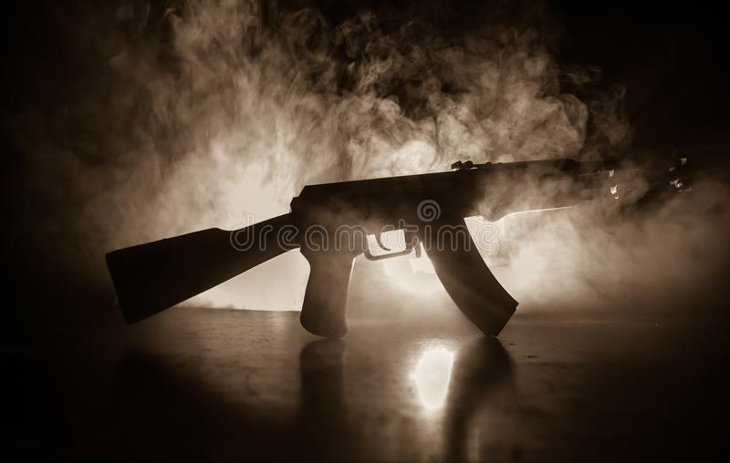 Silhouette of assault riffle on toned foggy background. War concept. Russian military weapon on table. Selective focus stock photo
