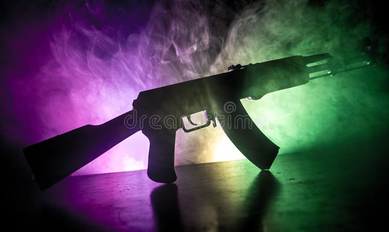 Silhouette of assault riffle on toned foggy background. War concept. Russian military weapon on table. Selective focus royalty free stock photos