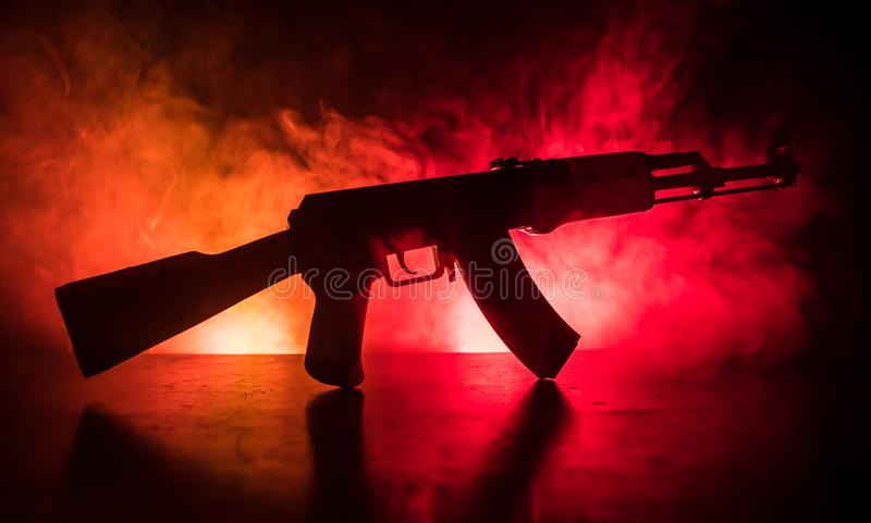 Silhouette of assault riffle on toned foggy background. War concept. Russian military weapon on table. Selective focus stock image