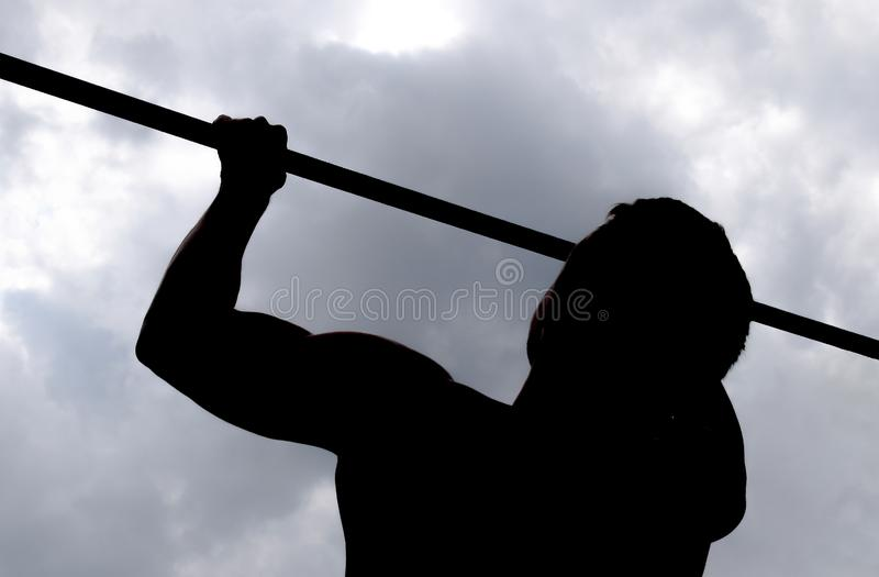 Silhouette of an athlete on a bar. The man pulls himself up on the bar. Playing sports in the fresh air. Horizontal bar royalty free stock photos