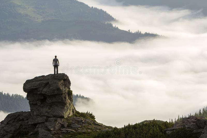 Silhouette of athletic climber tourist on high rocky formation on mountain valley filled with white puffy clouds and fog and. Covered with evergreen forest stock photo