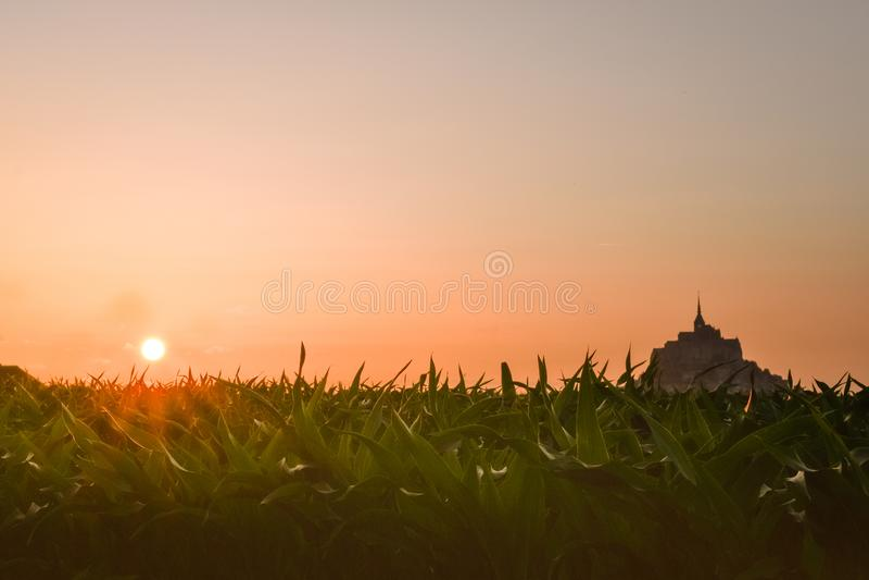 Silhouette au coucher du soleil des terres cultivables de Mont Saint Michel, France image stock