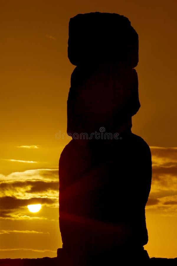 Silhouette av en moai mot orange soluppgång arkivbilder
