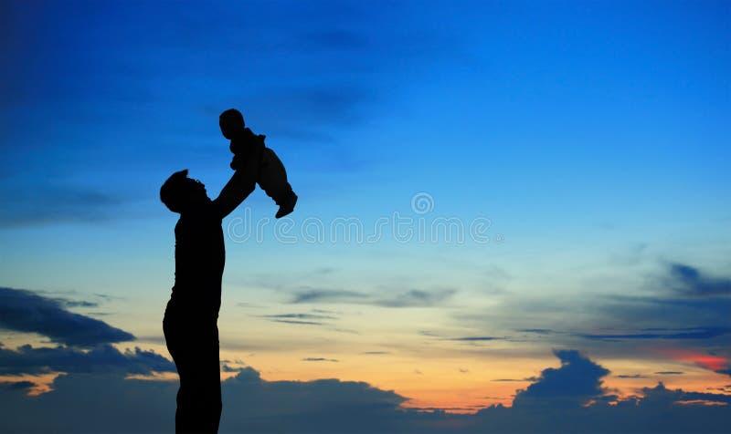 Silhouette av fadern och barnet på sommarsolnedgång fotografering för bildbyråer