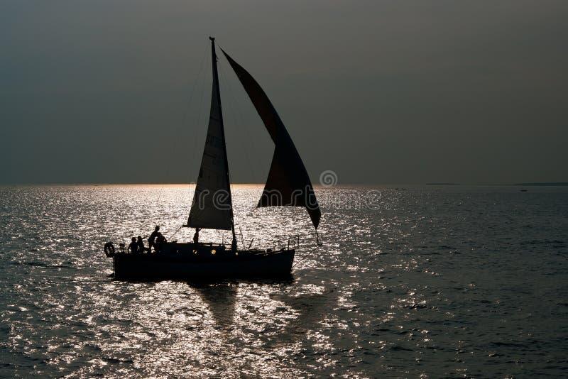 Silhouette av segelbåten i solnedgång på havet royaltyfri bild