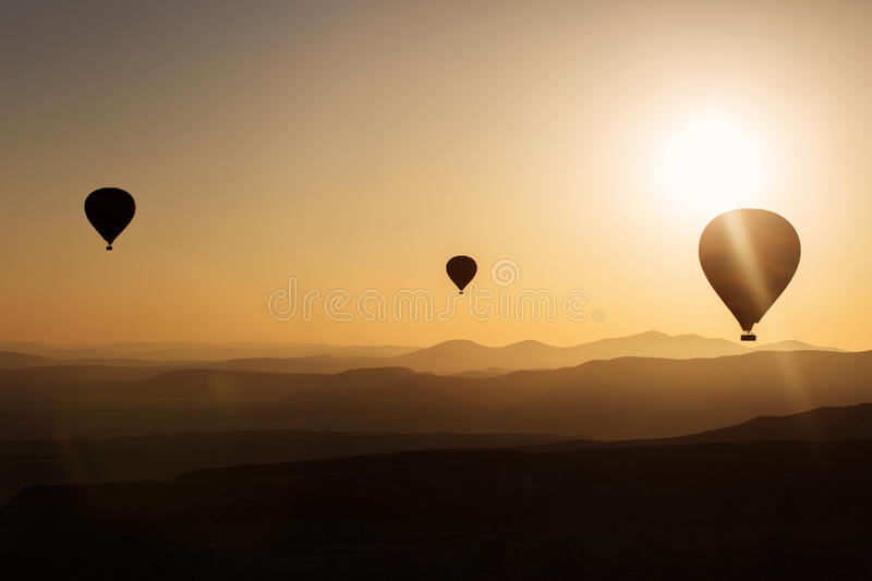 Silhouette of balloons with sunrise in background, aerial view stock photo