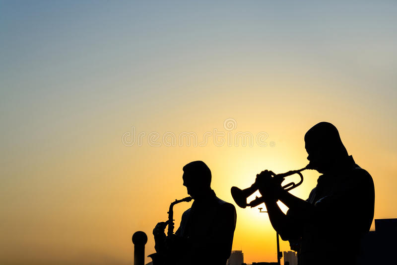 Silhouette of band playing the music. At sunrise stock image