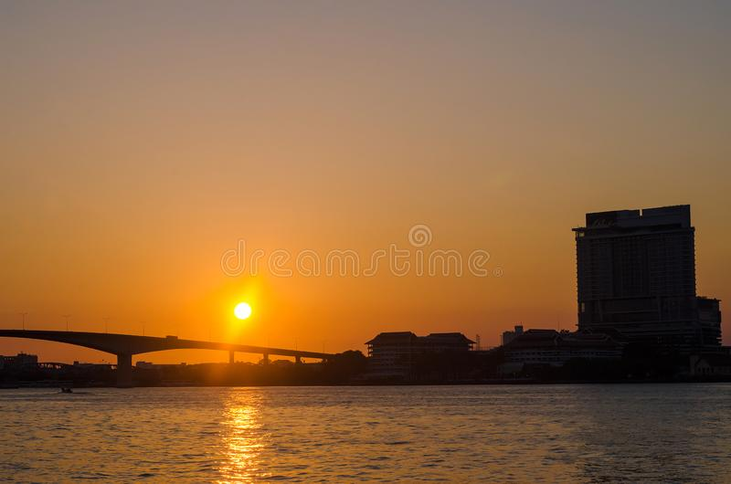 Silhouette of Bangkok Transportation at Sunset with Building along the river royalty free stock image
