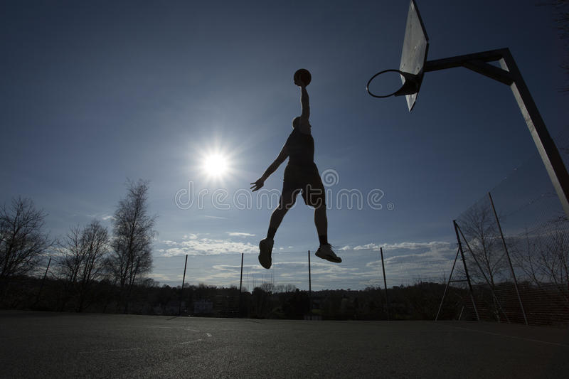 Silhouette basketball player in mid air about to slam dunk. A silhouette of a basketball player in mid air about to dunk the ball on an outdoor court stock photos