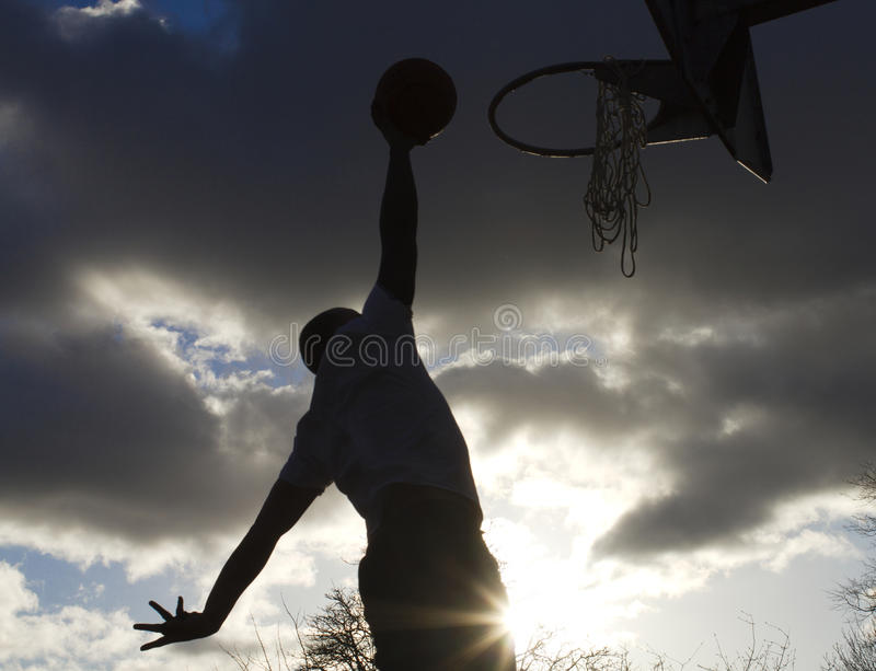Basketball Dunk Silhouette. Silhouette of a basketball player about to slam dunk with a natural sun flare stock photography