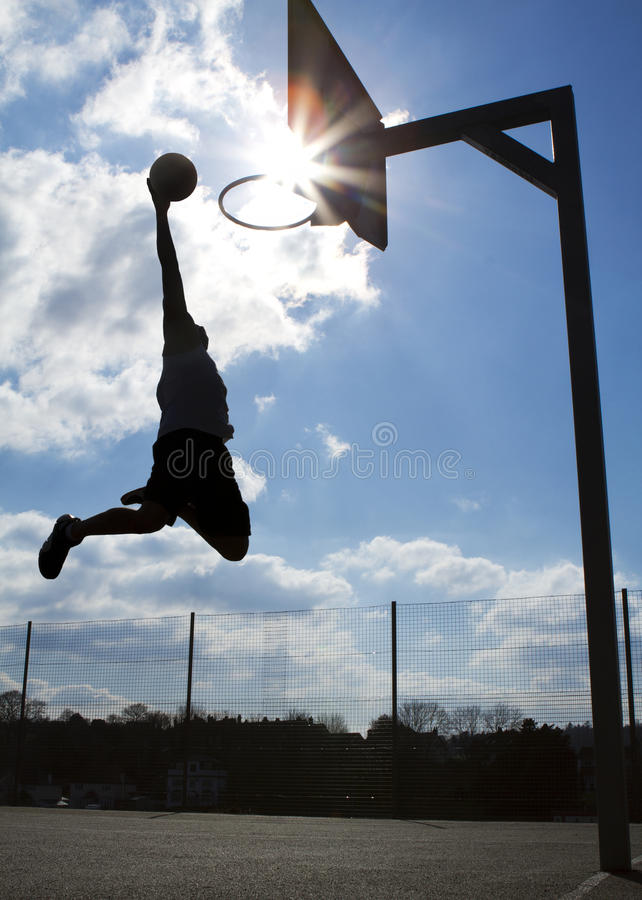 Basketball Dunk Silhouette. Silhouette of a basketball player about to slam dunk with a natural sun flare royalty free stock photo