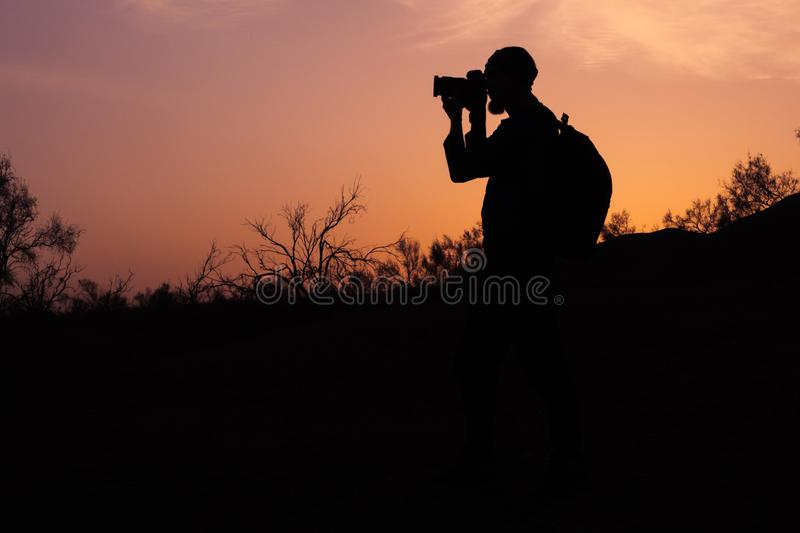 Silhouette a bearded photographer taking photo of sunset light royalty free stock photos