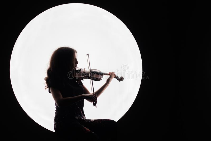 Silhouette of a beautiful brunette girl playing the violin. Concept for music news. Copy space. White circle as the moon stock photography