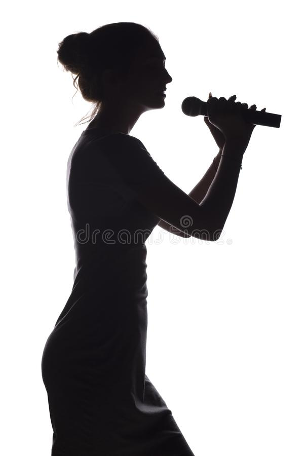 Silhouette of girl singing into microphone, profile of young woman face performing lyric song on white isolated background. Silhouette of beautiful girl with royalty free stock image