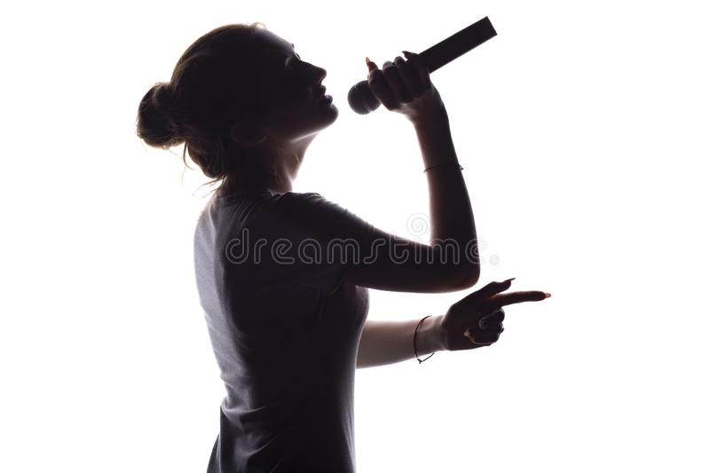 Silhouette of beautiful girl with hand-picked hair singing into microphone, profile of young woman face performing lyric song on. White isolated background royalty free stock photo