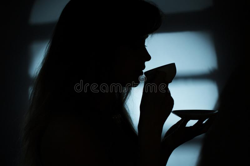 Silhouette of a girl near a window with a cup of hot drink royalty free stock photography
