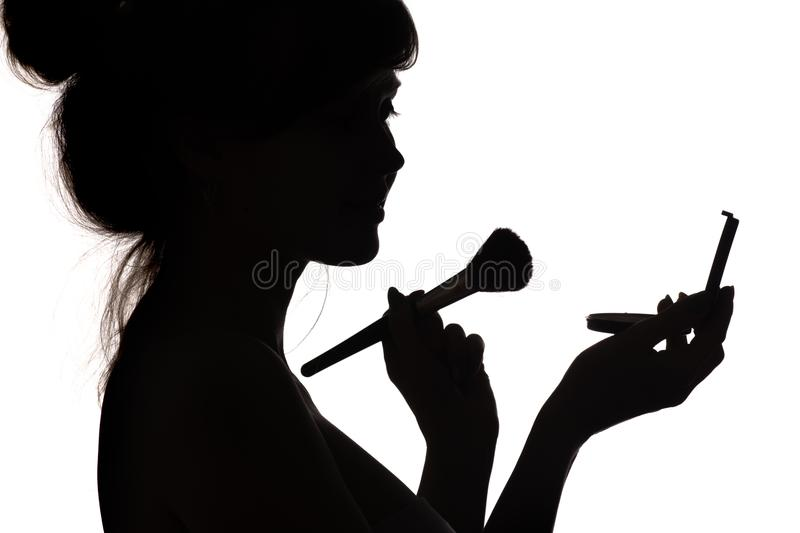 Silhouette of girl doing make-up, profile of female face on white isolated background, concept of fashion and beauty royalty free stock photo