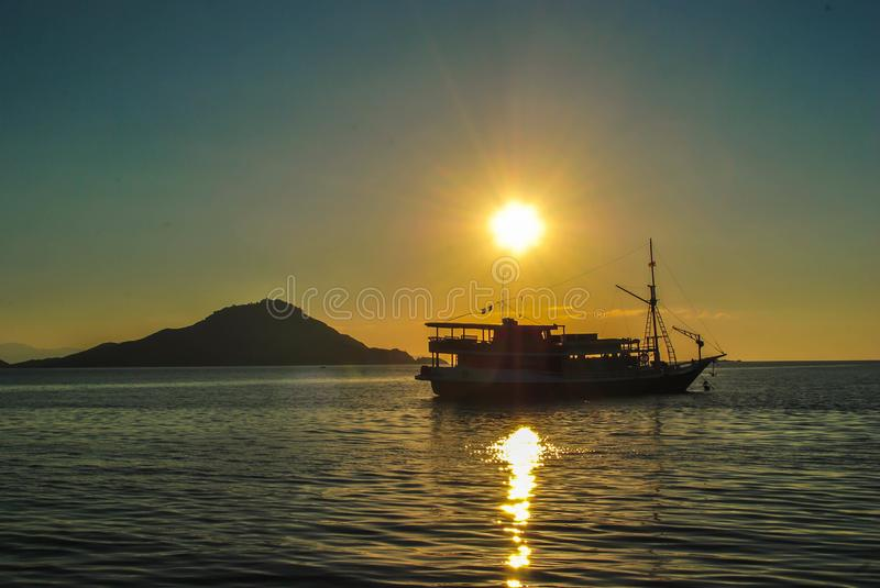Silhouette of beautiful sunset with fishing boat. Beautiful Sunset in tropical Komodo island, Labuan Bajo, Fores, Indonesia stock photography