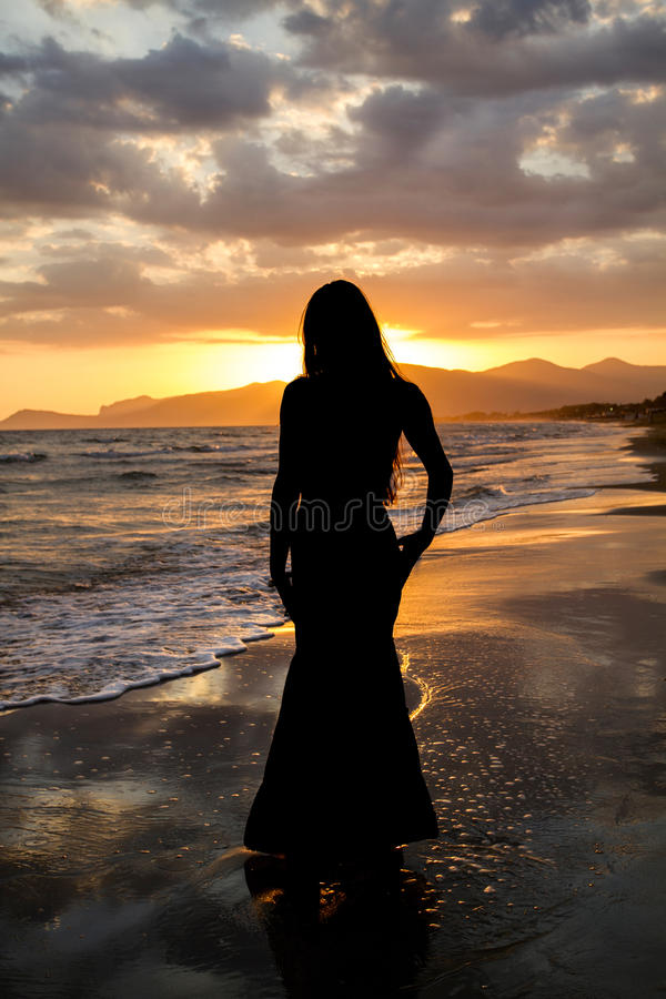 Silhouette of a beautiful woman on the background of the sea at sunset . stock photos