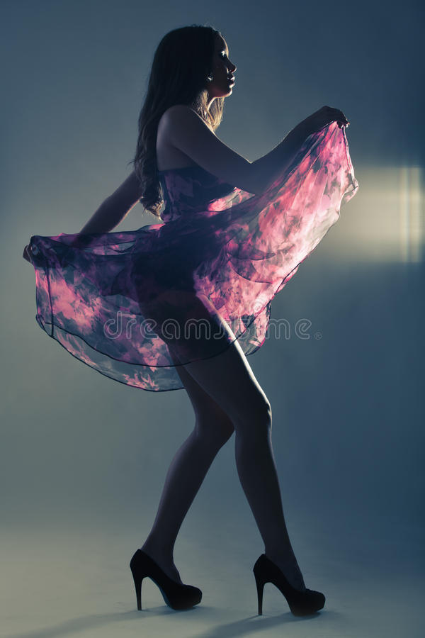 Silhouette of a beautiful woman dancing in purple dress in studi stock images