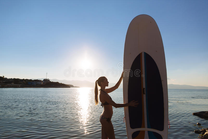 Silhouette of a beautiful woman on stand up paddle board. SUP, concept lifestyle, sport stock photos