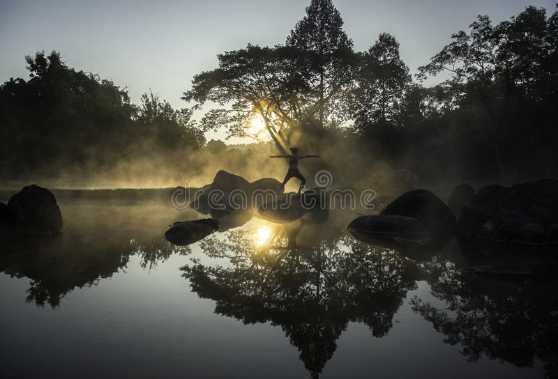 Silhouette of a beautiful Yoga woman in the morning stock photography