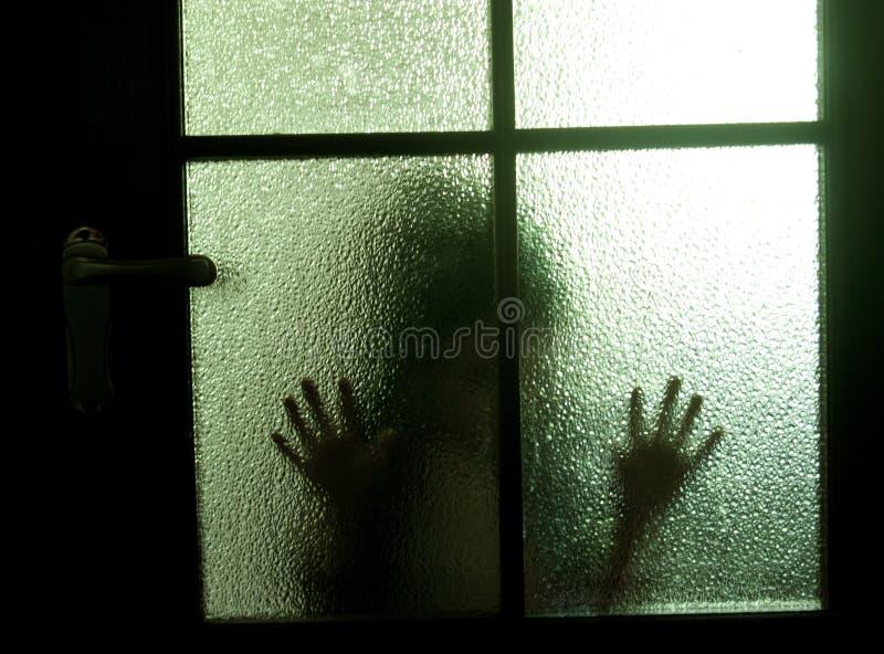 Silhouette behind a door stock photos