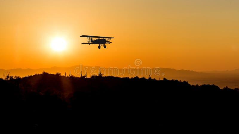 Silhouette of a bi-plane flying over desert royalty free stock image