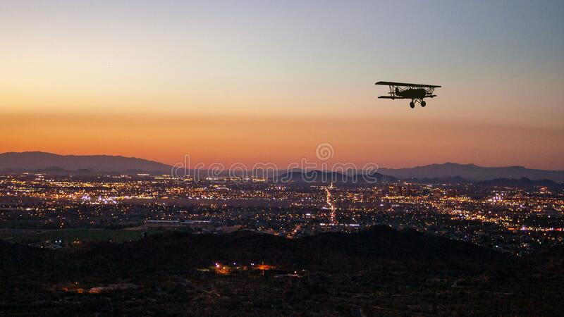 Silhouette of a bi-plane flying over Phoenix, AR royalty free stock photos
