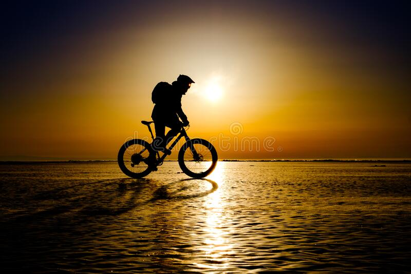 Silhouette of bicyclist on the ice of frozen lake royalty free stock photo