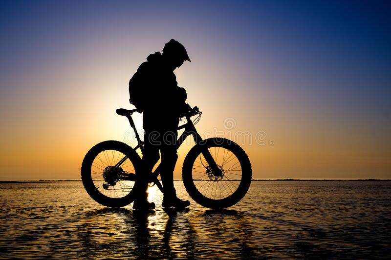 Silhouette of bicyclist on the ice of frozen lake royalty free stock images
