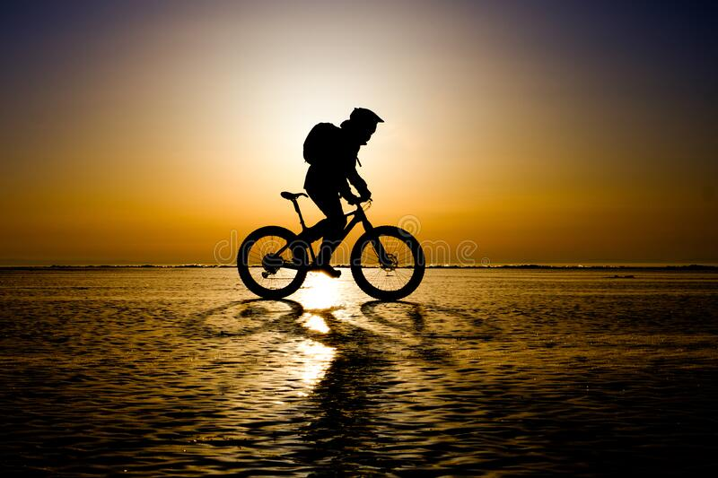 Silhouette of bicyclist riding on the clear ice stock photos
