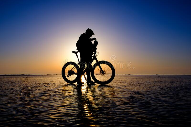 Silhouette of bicyclist standing on the clear ice royalty free stock photo