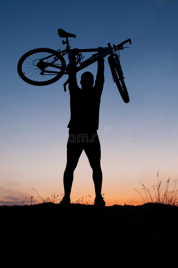 Silhouette of biker. Silhouette of a biker holding his bicycle stock photography