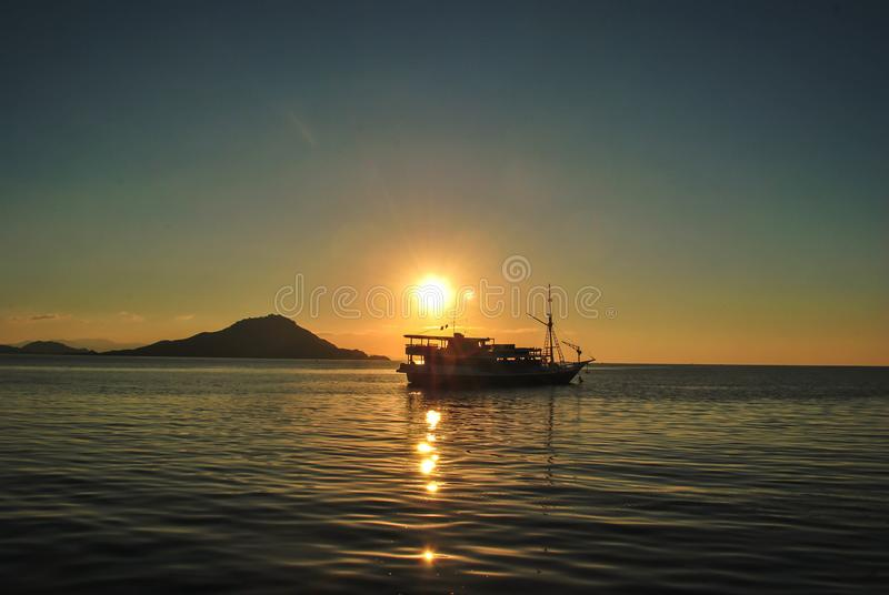 The silhouette of a boat against a sunset sky in tropical Komodo island, Labuan Bajo, Fores, Indonesia stock photos