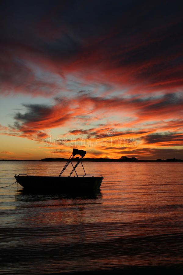 Silhouette of a boat in water sunset royalty free stock images