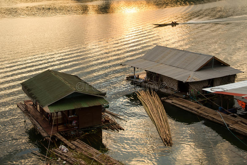 Silhouette of Boating Man boat ride in the river at sunset in Sa. Ngkhlaburi ,Thailand stock photography