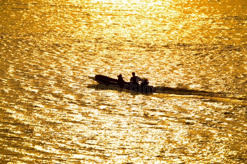 Silhouette of a boatman in river on golden sunshine royalty free stock images
