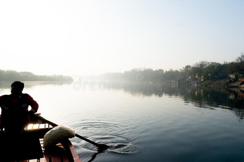silhouette of boatsman rowing out into the yamuna ganga river in the morning royalty free stock photography
