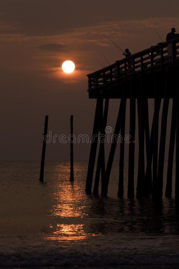 Silhouette Of A Boy Fishing From A Pier At Sunrise Royalty Free Stock Images