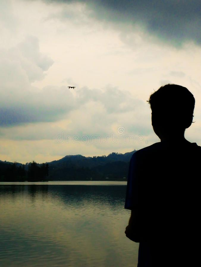 Silhouette of a boy flying a drone over a lake in an overcast day stock images