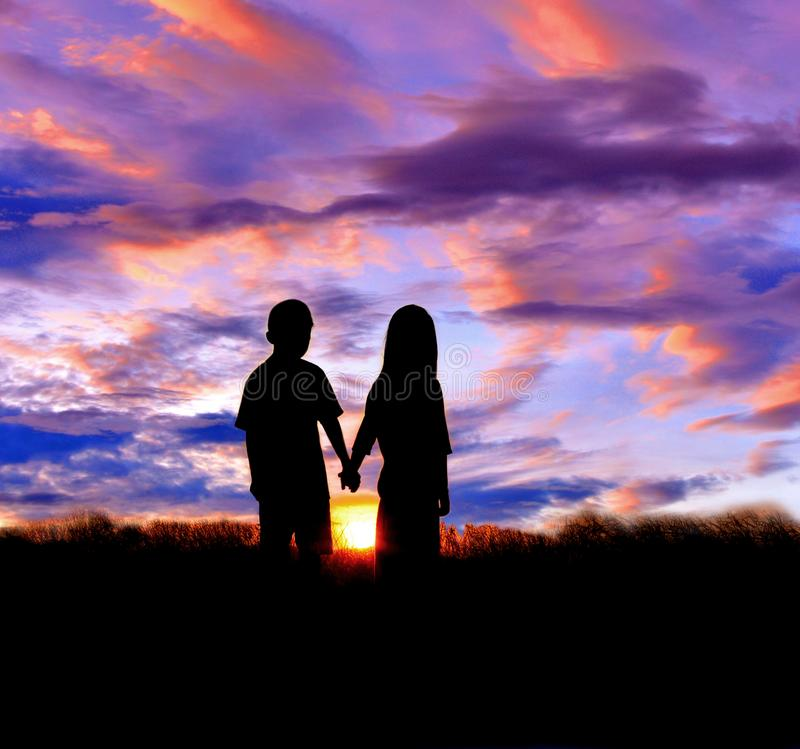 Silhouette of boy and girl stand hand in hand to watch the sunset stock photos