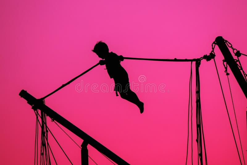 Silhouette Of Boy Jumping On Trampoline On Evening Red, Pink Colorful Sunset Sky stock photo