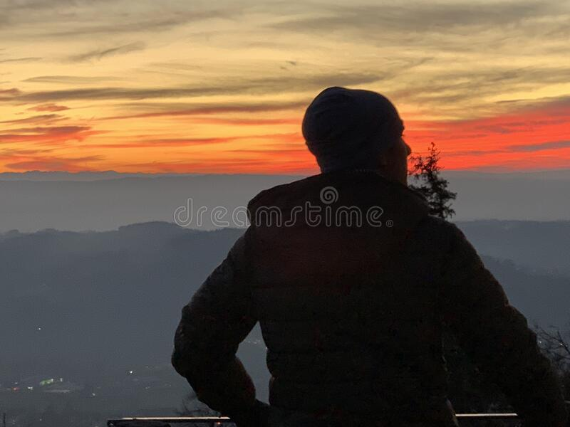 A silhouette of a boy observing landscape in sunset light. Uetliberg Zurich Switzerland in winter. A silhouette of a boy observing landscape in sunset light stock images