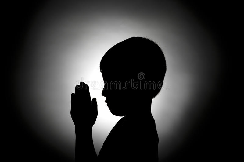 Silhouette of boy in prayer. The silhouette of a young boy bowed in prayer royalty free stock photos