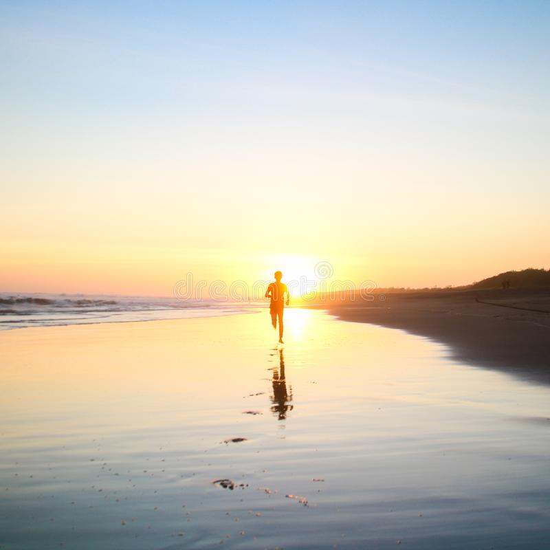 Silhouette of Boy Running in Body of Water during Sunset stock image