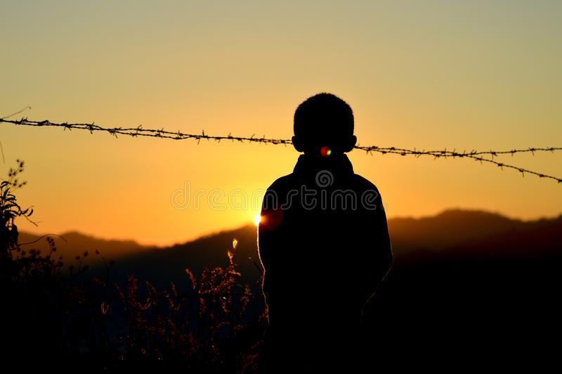 Silhouette of Boy Standing Near Barbed Wire Fence during Golden Hour stock images